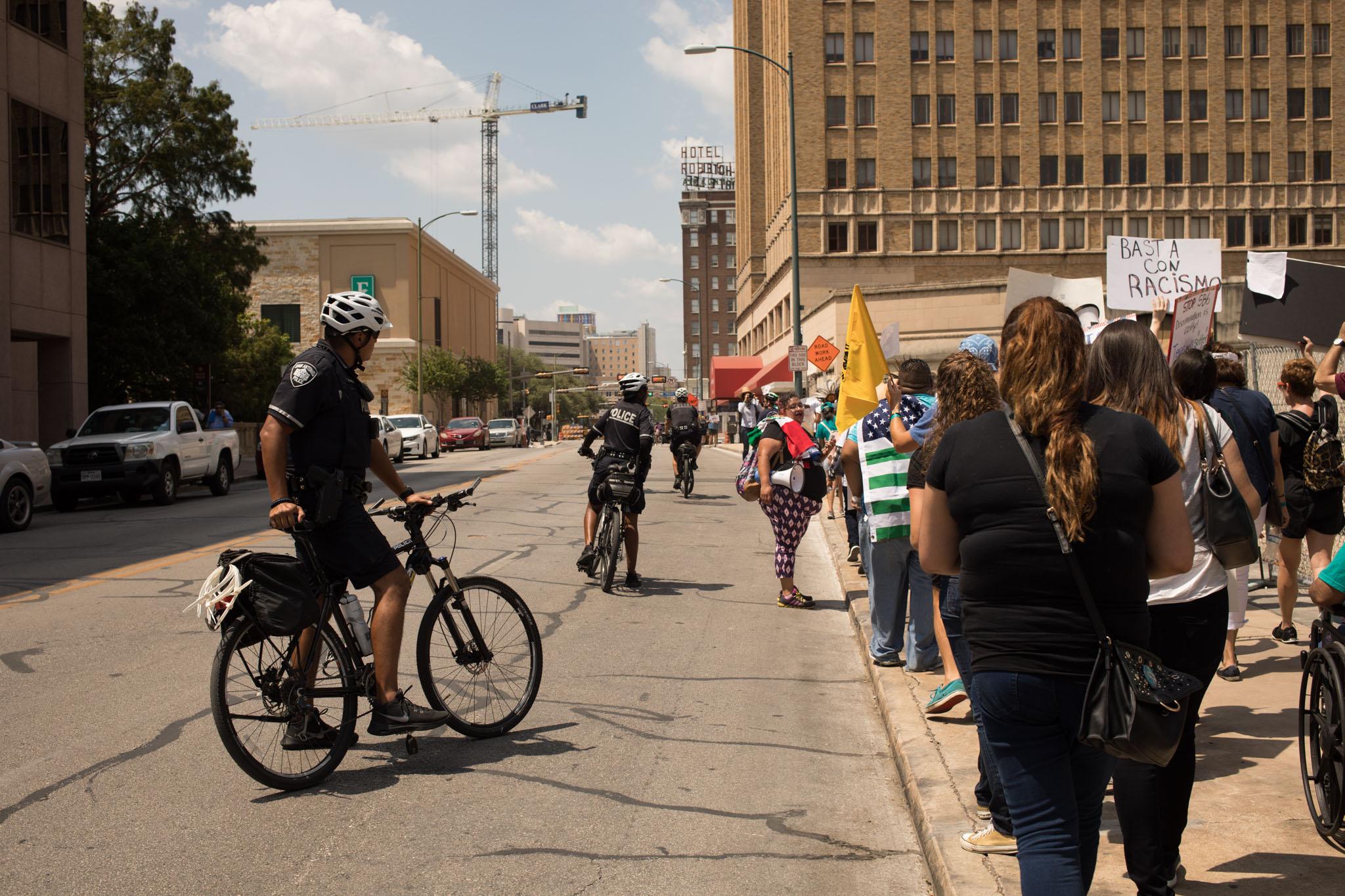 Police help protestors against SB4 stay safe on the sidewalk.