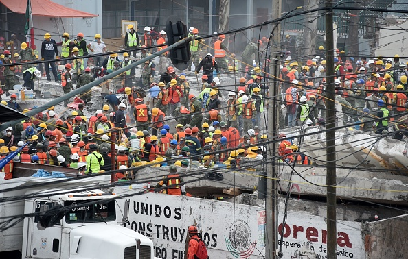 Volunteers, soldiers and marines remove rubble from a flattened building in Mexico City on September 22, 2017 three days after a strong quake hit central Mexico.