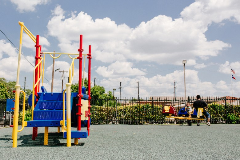 A father and son play in the playground at the Alazan-Apache Courts.