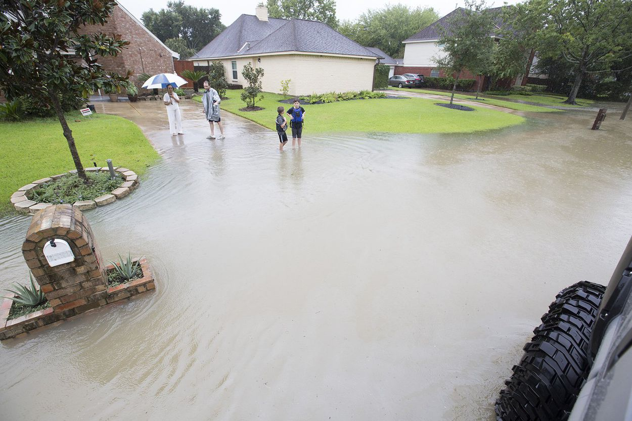 Chris Ginter, center, tries to convince a resident of a flooded neighborhood near Buffalo Bayou in Houston to evacuate in his monster truck on Tuesday, Aug. 29, 2017.