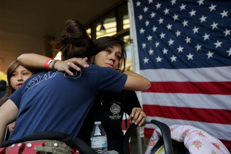 Jennifer Deem is hugged by San Antonio fire fighter Dana Zamarripa who worked with her husband Scott Deem at Station 35.