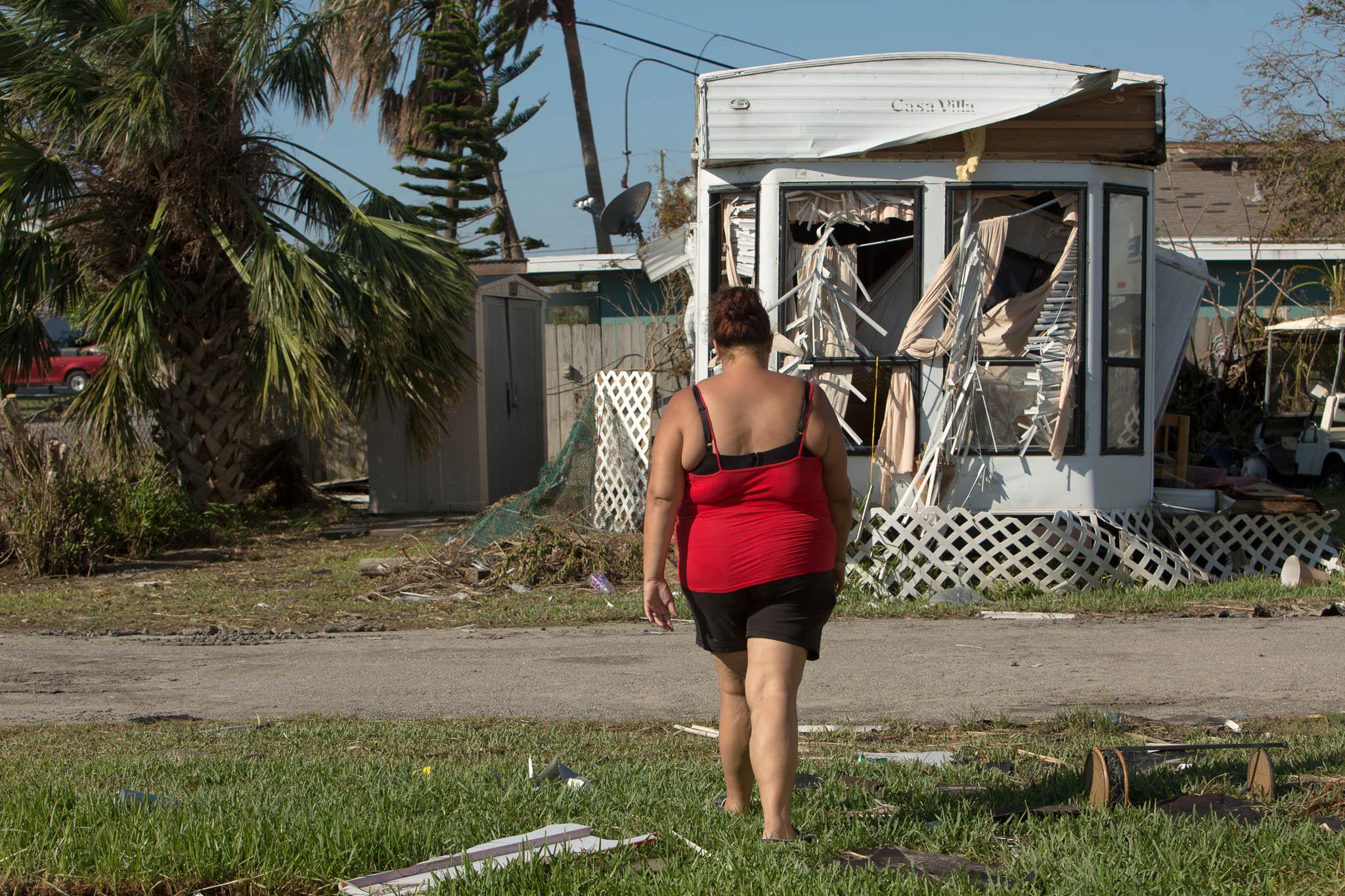 Jessica Williford walks towards a damaged mobile home at Beacon Trailer Park in Port Aransas, Texas.
