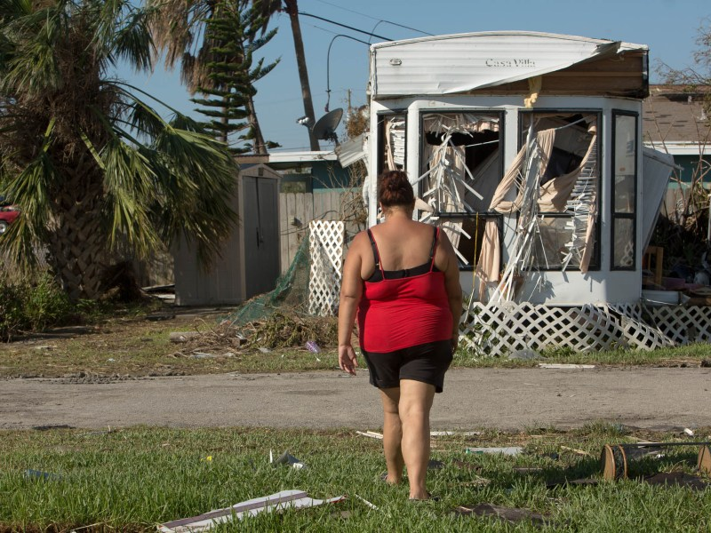 Jessica Williford walks towards a damaged mobile home at Beacon Trailer Park in Port Aransas, Texas.