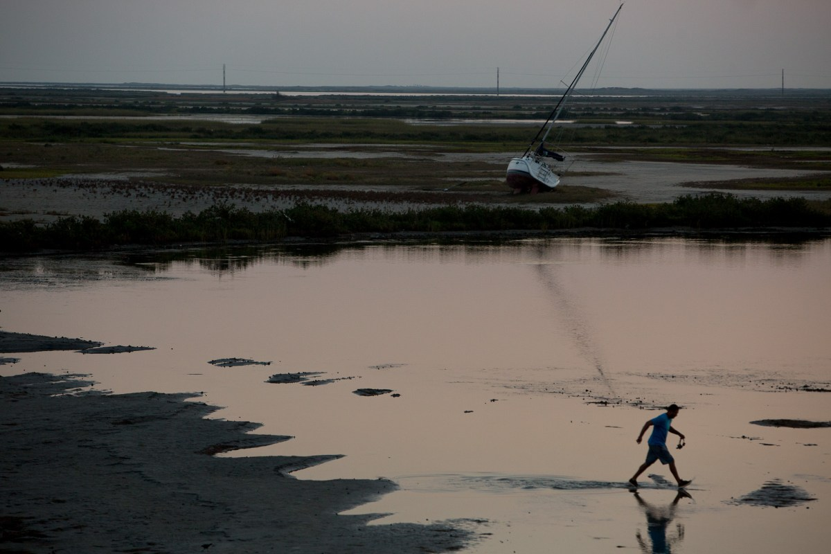 A fisherman takes large steps across wetlands outside of Port Aransas, Texas as a beached boat washed onto dry land.