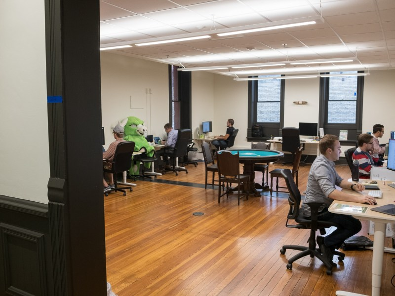 Employees can be found in multiple rooms with dedicated conference rooms and private workspaces.