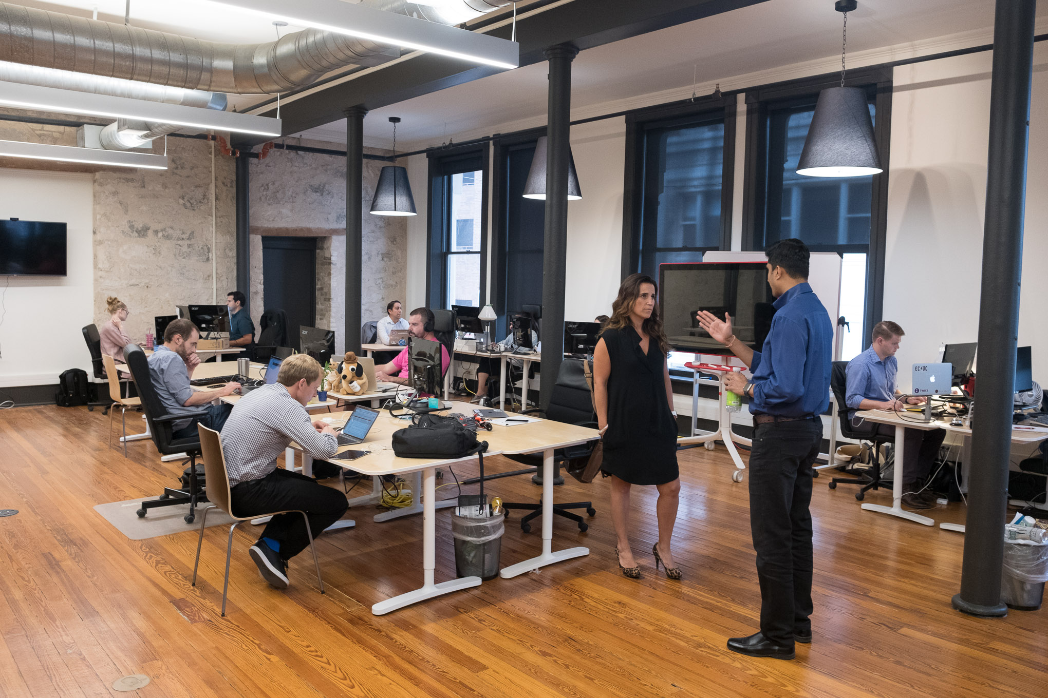 Scaleworks employees work in a large open-air office space renovated at the Savoy building.