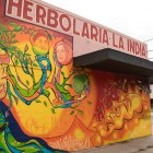 The westward-facing facade of La India Herbs botanica is painted with a colorful mural.
