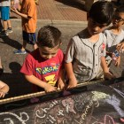 Children play a piano decorated in chalk design at Chalk It Up.