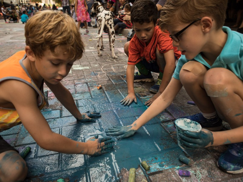 (From left) Brian Levin, 8, Axel Peterson, 7, and William Abag, 7, smear chalk and paint onto Houston Street at Chalk It Up.
