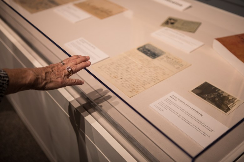 Daughters of the Republic of Texas Library Collection Committee Chairman Susan Riedesel places her hand on a display case.