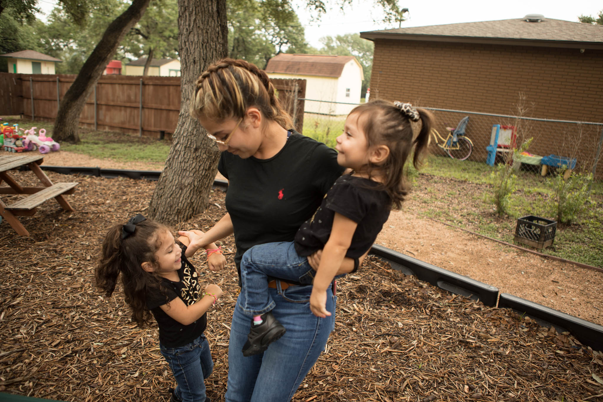 Briana Zapata, 17, (center) shares a laugh on the playground with her daughters Natalie, 3, (left) and Daniella, 1, at the SJRC Texas Pregnant Parenting Teen Program.