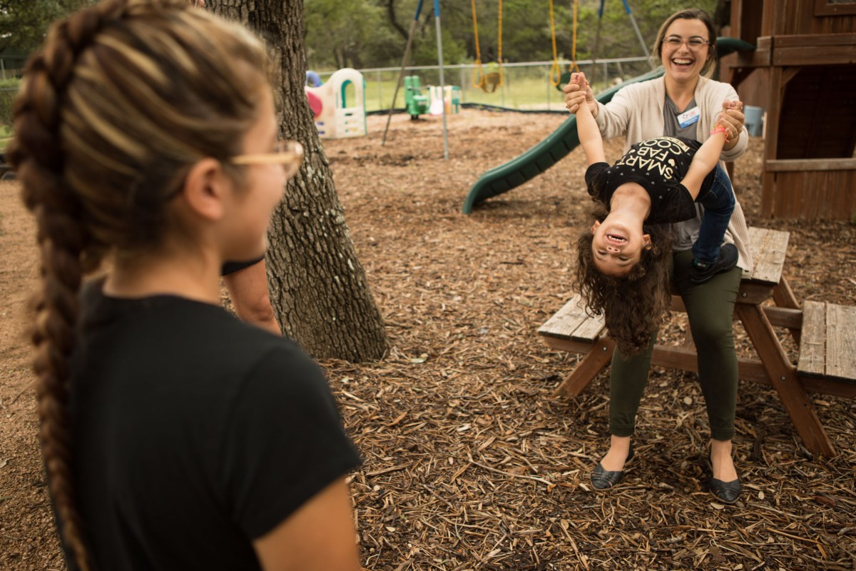 SJRC Texas Case Manager Hailey Conner plays with Natalie Zapata, 3, as her mother Briana Zapata, 17, watches at SJRC Texas Pregnant Parenting Teen Program.