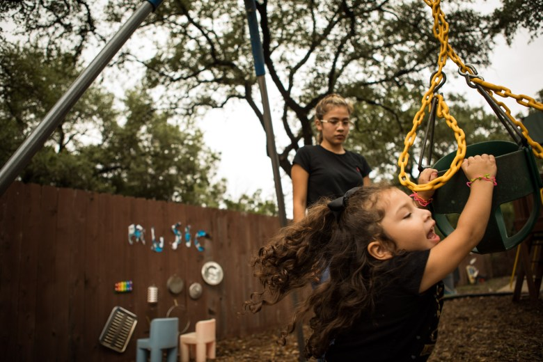 Briana Zapata, 17, (left) watches her daughter Natalie, 3, run around in circles with a swing at the SJRC Texas Pregnant Parenting Teen Program.