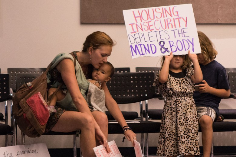 (From left) Maureen Galindo, Brigid Galindo, 1, Katie Galindo, 5, and AJ Galindo, 7, prepare their signs to hold up the first Mayor's Housing Policy Task Force meeting at San Antonio Central Library.
