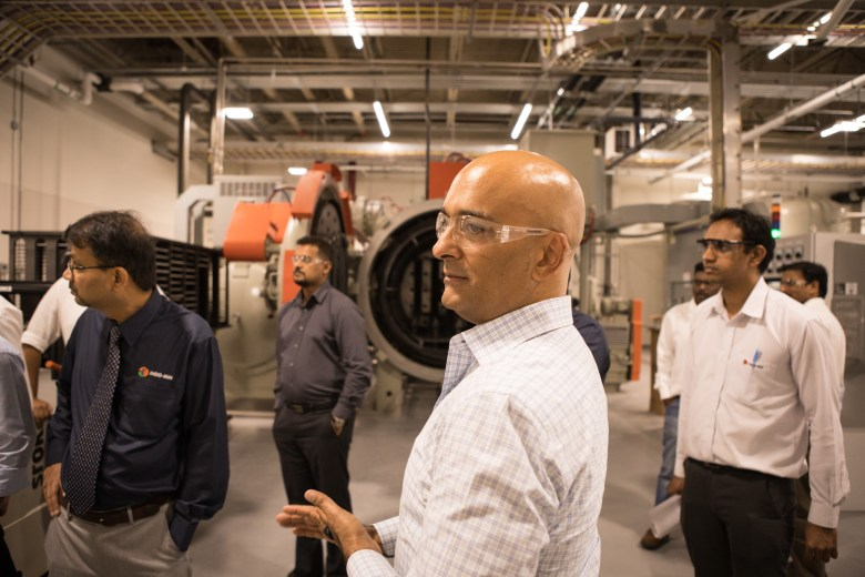 Indo-MIM CEO Krishna Chivukula Jr. stands with his employees near the sintering furnace in their new factory at Port San Antonio.
