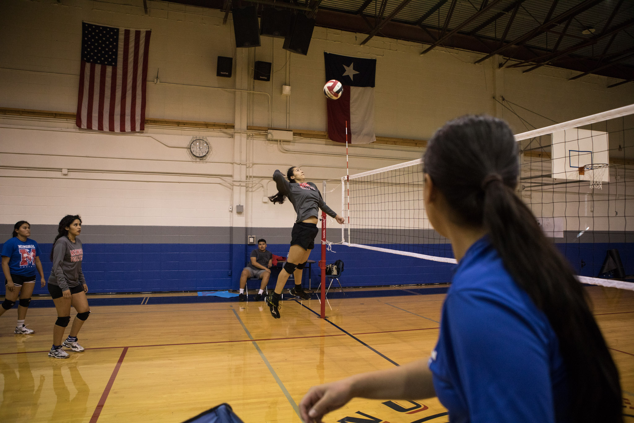 Tiffany Lopez spikes the volleyball during practice at Memorial High School as her coach Samantha Mendez looks on.