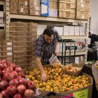 Ali Baba International Food Market customers place persimmons into plastic bags.
