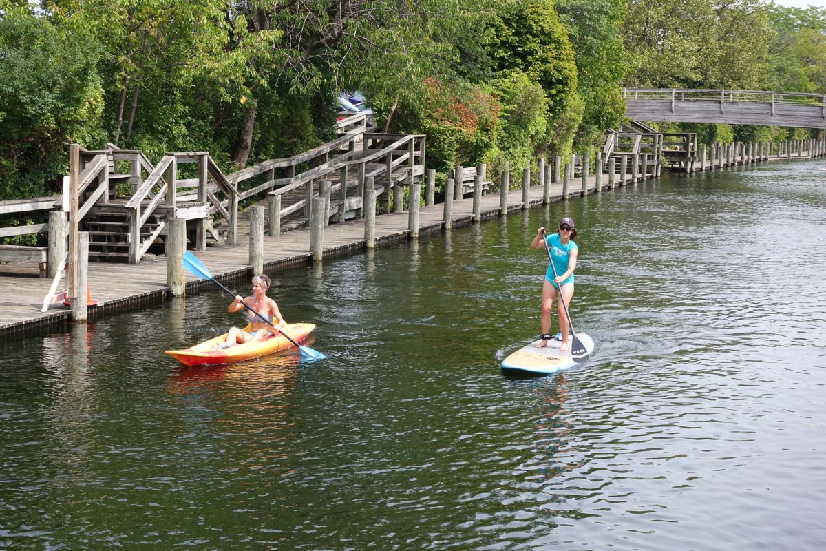 A kayaker and paddle boarder enjoy a Sunday afternoon in on the Black River in South Haven, Michigan.