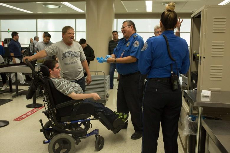 Troy and Lee Joplin talk with TSA officer David Gonzalez as he inspects Troy's wheelchair.