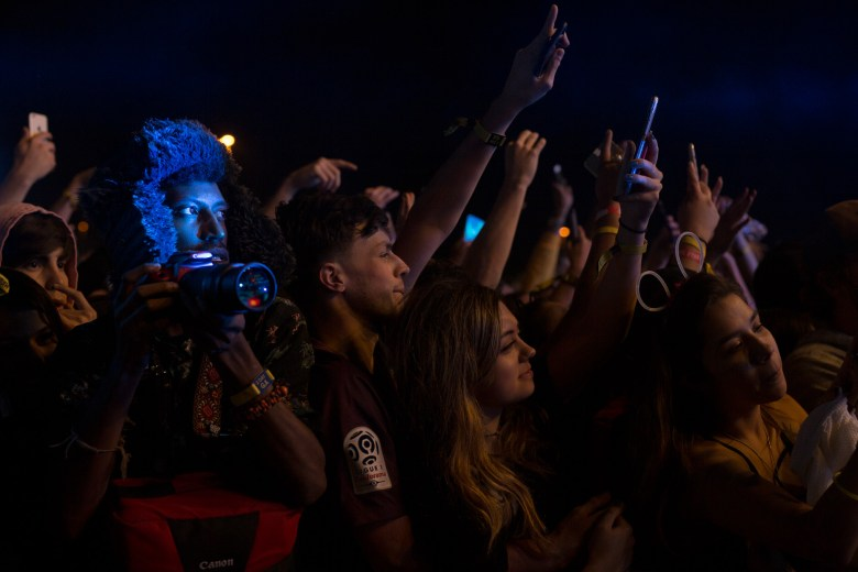 Attendees use their cell phones and cameras to photograph and record the performance by Wiz Khalifa.