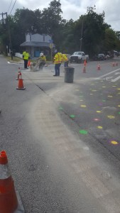 City workers spread sand on the illegal crosswalk markings and use a grinder to remove the paint.