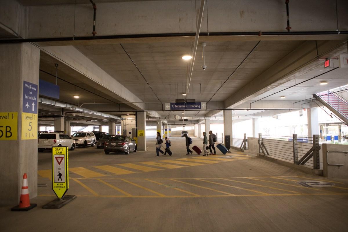 Passengers walk along the walkway from the long-term parking garage through the short-term parking garage at the San Antonio International Airport.