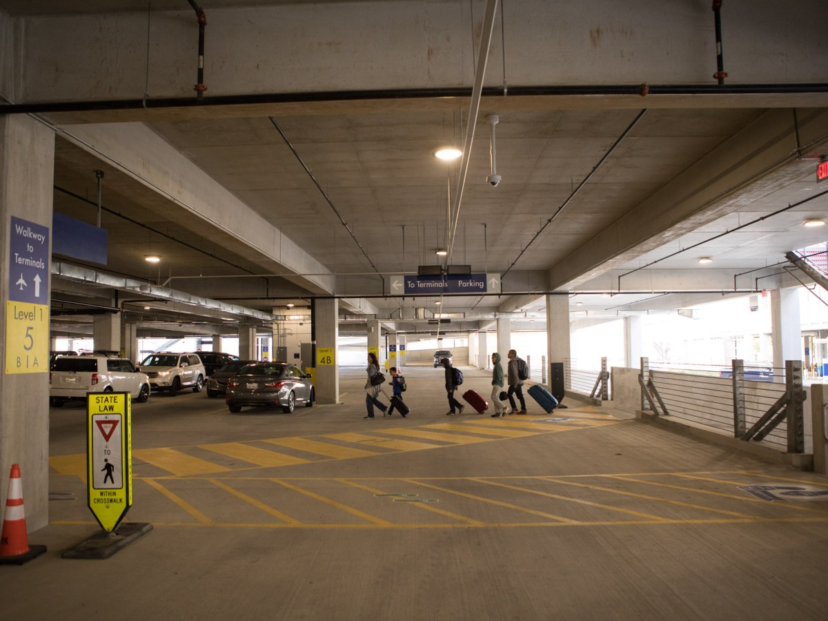 Passengers walk along the walkway from the long-term parking garage through the short-term parking garage at the San Antonio International Airport.