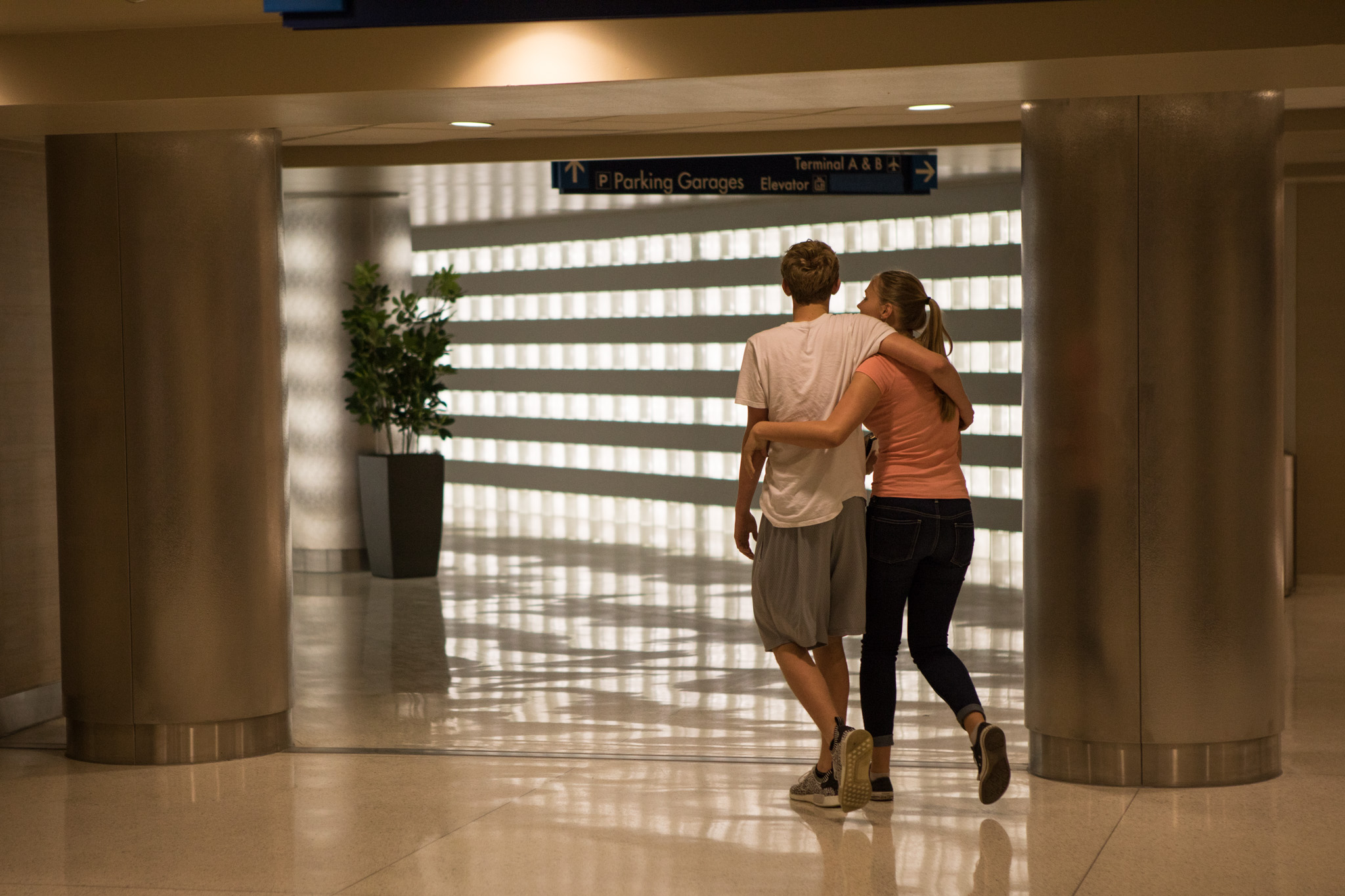 A couple enters the walkway leading from the airport terminal to the short-term parking garage at the San Antonio International Airport.
