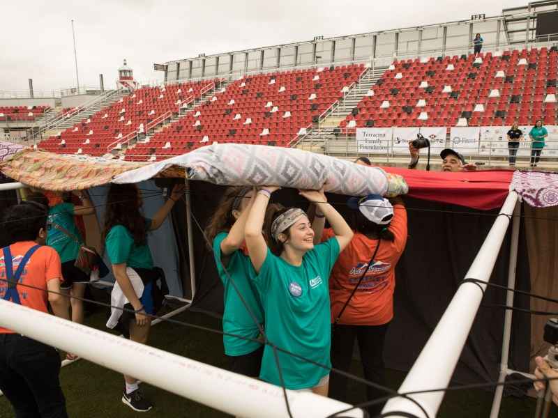 Samuel Clemens Dance Team Dancer Kyleigh Koster, 17, helps unroll blankets to construct the world's largest blanket fort for autism awareness at Toyota Field.