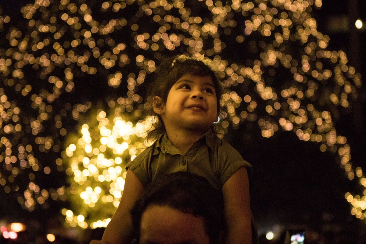 Aaliyah Flores, 2, sits on her grandfather's shoulders during the 33rd Annual H-E-B Christmas Tree Lighting celebration in Travis Park.