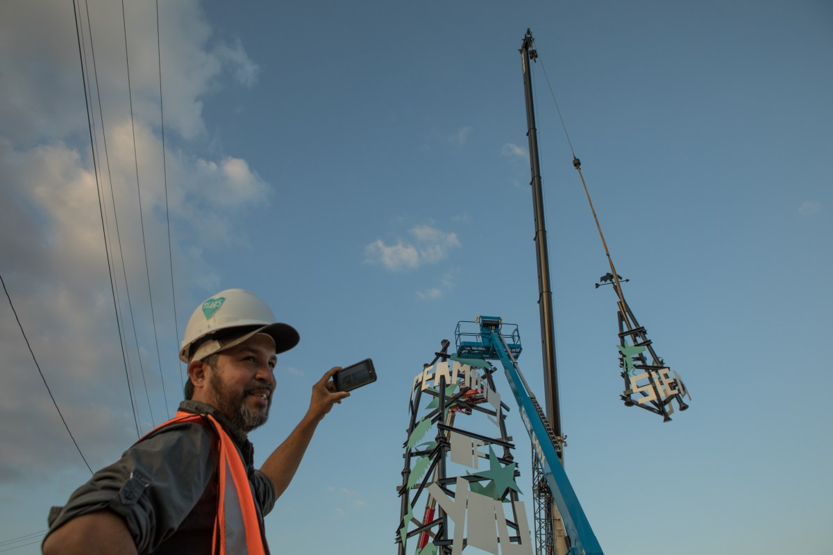 Local artist Cruz Ortiz shares a live stream as the last section of the Dream Song Tower is hoisted towards the top of the structure.