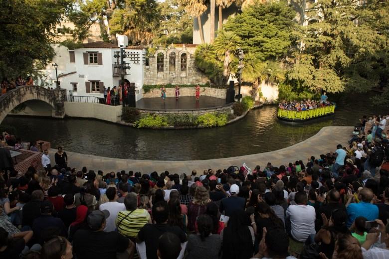 A new San Antonio River Barge passes the dance performances at Arneson River Theatre during Diwali San Antonio: Festival of Lights.
