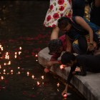 Attendees place their candles into the San Antonio River during the Diya Ceremony at Diwali San Antonio: Festival of Lights.