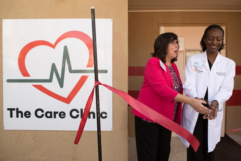 (From left) San Antonio AIDS Foundation CEO Cynthia Nelson and San Antonio AIDS Foundation Medical Director Wari Allison cut a ribbon to honor the Care Clinic, the first outpatient HIV healthcare facility on the East Side.