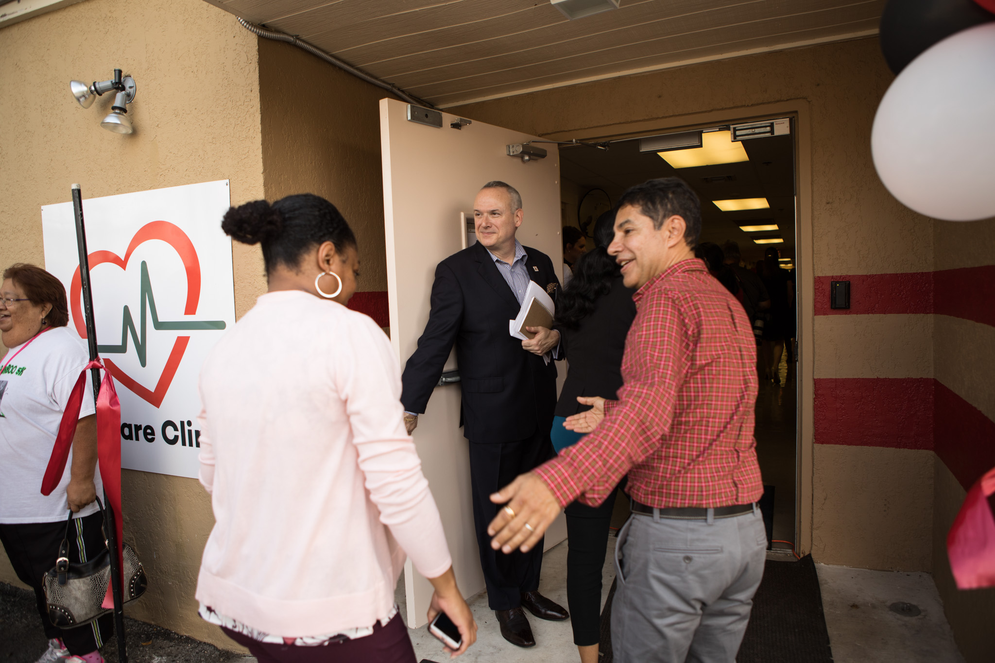 San Antonio AIDS Foundation Vice President of Communications Ken Slavin (center) holds the door open for (from left) San Antonio AIDS Foundation Chief Operations Officer Aja Jenkins and Mental Health Councelor Francisco Ramirez enter an open house for the Care Clinic.