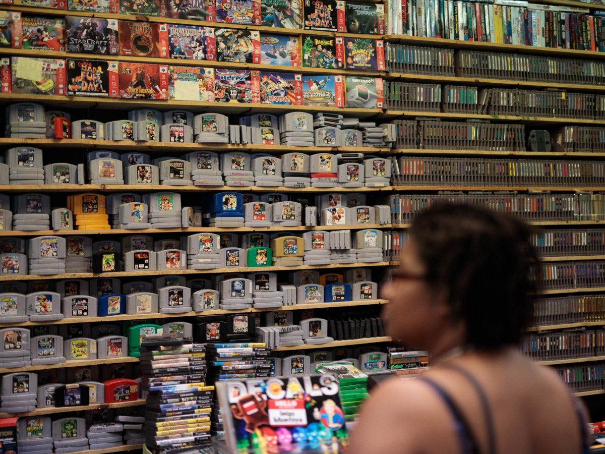 Customers of Propaganda Palace walk in to see thousands of retro video games stacked on shelves.