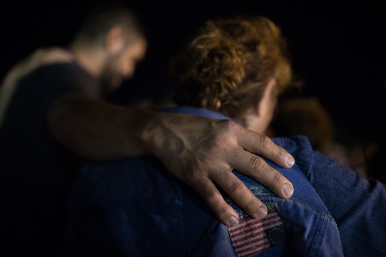 Community members embrace for a word of prayer during the vigil.