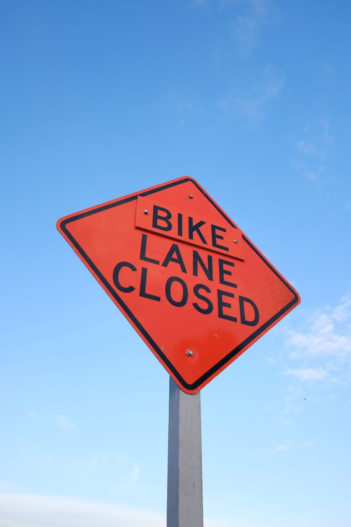 A sign posted informing cyclists that an upcoming bike lane is closed.