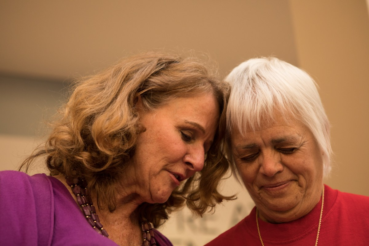(From left) Louise Locker, Elf Louise Christmas Project founder, and LeAnn Crim, Elf Louise Christmas Project Treasurer of the Board, say a prayer before beginning the WOAI 1200 Elf Louise Radiothon.