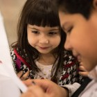 Marcos Salas, 10, (right) helps Memphys Villarreal, 4, write her letter to Santa at the 25th annual H?E?B Feast of Sharing holiday dinner.