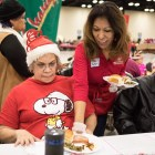 Cynthia Teniente-Matson, Tricentennial commission president, serves hot meals at the 25th annual H?E?B Feast of Sharing holiday dinner.