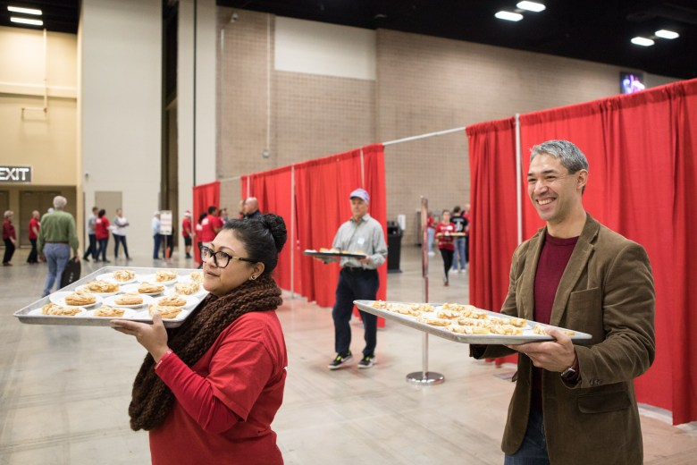 (From left) Erika Prosper and Mayor Ron Nirenberg serve dessert at the 25th annual H?E?B Feast of Sharing holiday dinner.