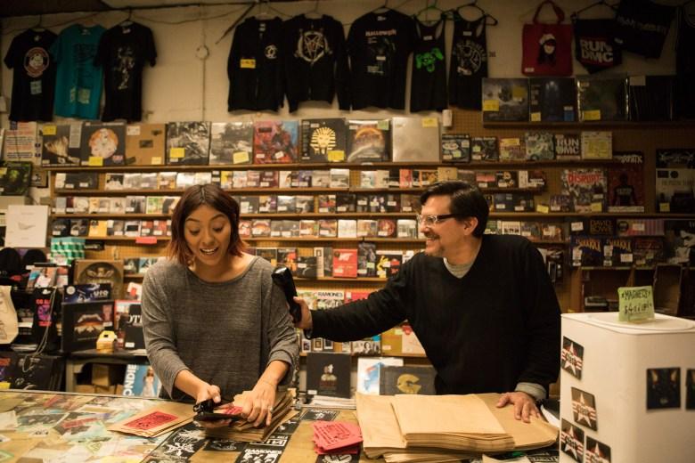 Hogwild Records Cashier Isabela Martinez and Manager Steven Alejandro share a joke behind the front desk.