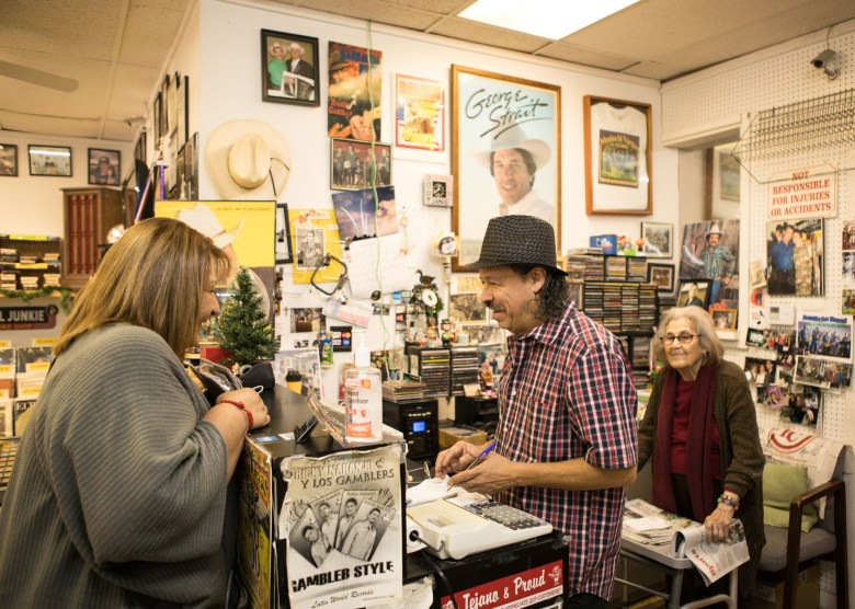 (From right) Janie Esparza and her son Robert Esparza assist a customer with a purchase at Janie's Record Shop.