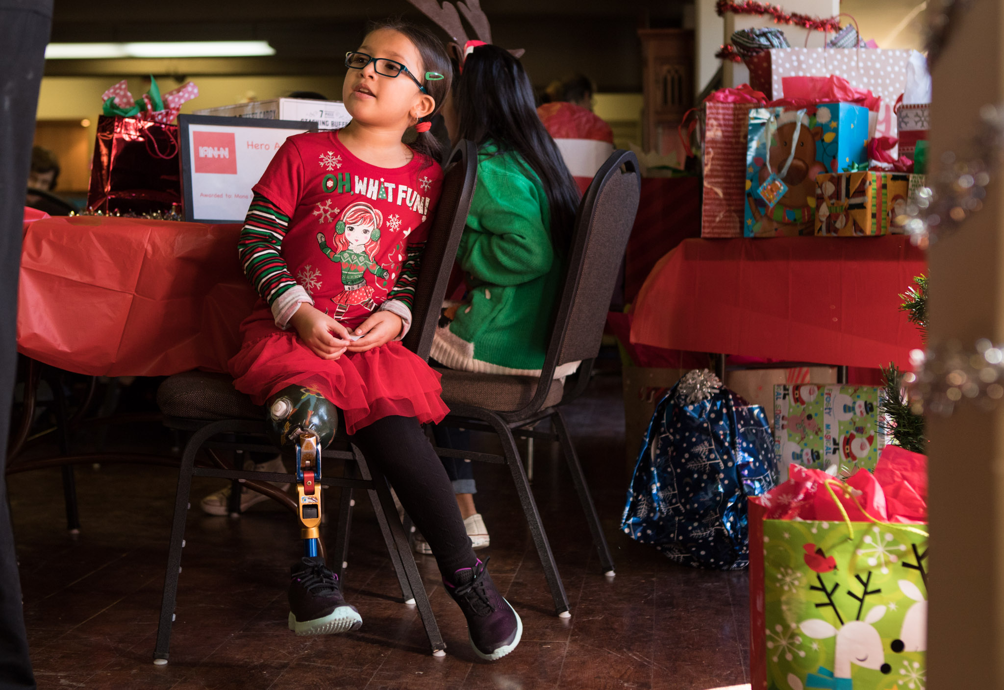 Azalia Sandoval helps with the gift exchange at the San Antonio Amputee Foundation Annual Holiday Luncheon.