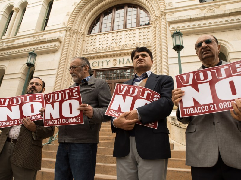 (From left) Mohammad Rana, Association of Convenience Store Retailers Founder, Jay Sharkh, Jamin Khan, and Khalid Bajwa hold signs protesting the Tobacco 21 Ordinance in front of City Hall.