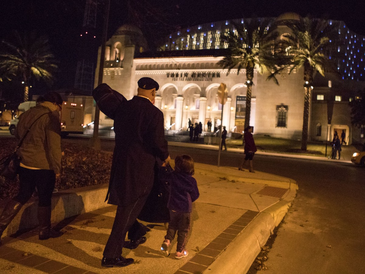 (From right) Arianna Huckaby, 3, San Antonio Symphony Principal Bassist Tom Huckaby, Alexandria Buckner, and David Huckaby, 6, walk down Jefferson Street on their way to the first of two Tricentennial concerts.