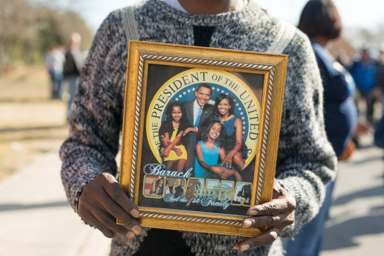 A march participant walks with a framed portrait of the Obama family.