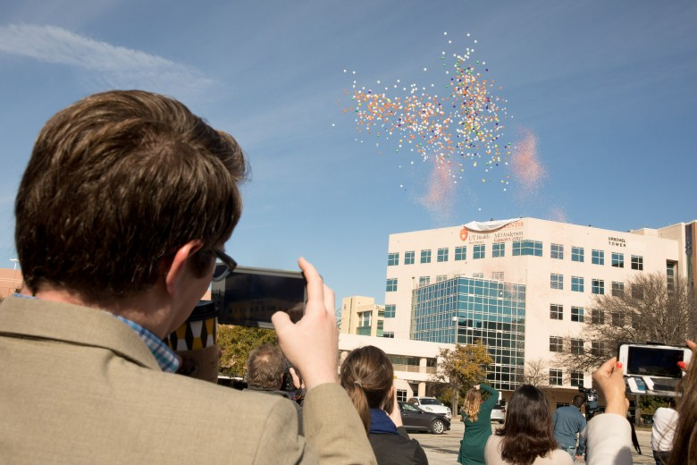 Balloons and confetti emerge from the newly named Mays Cancer Center.