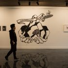 Mark Anthony Martinez looks at the mural Reconquista in the show Images of Power at Freight Gallery & Studios.